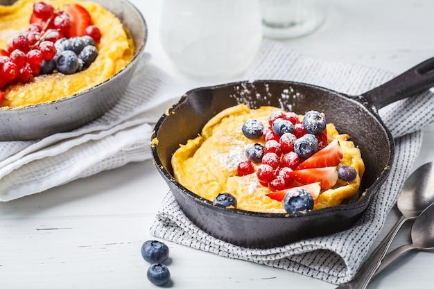 Pancake néerlandais avec des baies dans une poêle en fonte.