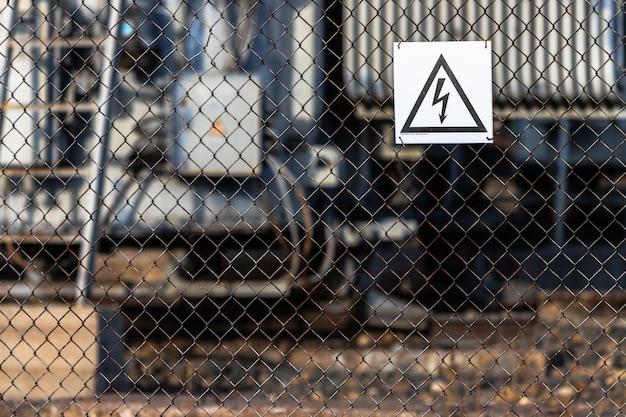 Une pancarte signalant les dangers de la haute tension électrique est accrochée au treillis métallique qui entoure le poste électrique.