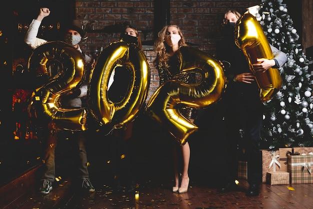 Pandémie de corona virus. concept de fête, de personnes et de vacances du nouvel an - femmes et hommes portant un masque médical de protection célébrant le nouvel an 2021