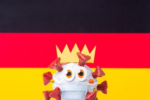 Pandémie de coronavirus en allemagne. modèle fait à la main de cellule covid-19 avec une couronne, portant un masque médical devant le drapeau de l'allemagne.