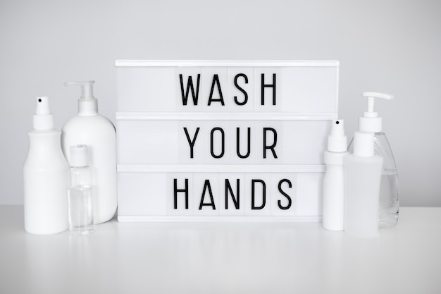 Pandémie de coronavirus et concept d'hygiène des mains - caisson lumineux avec message de lavage des mains et différentes bouteilles de désinfectant ou de savon liquide sur blanc