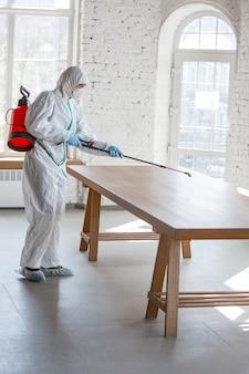 Pandémie de coronavirus. un désinfectant dans une combinaison de protection et un masque vaporisent des désinfectants dans la pièce.