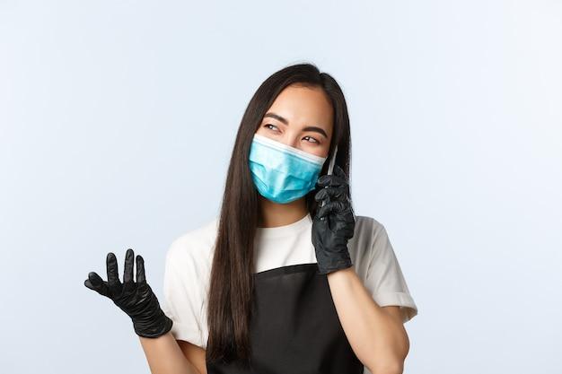 Pandémie de covid-19, café, petite entreprise et concept de prévention des virus. barista asiatique souriante et insouciante, employée en masque médical parlant sur téléphone portable.