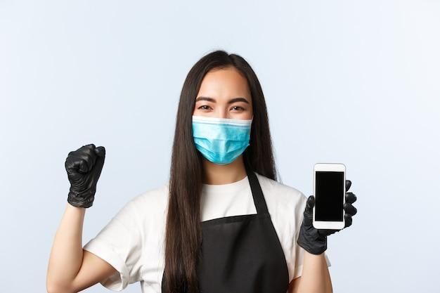 Pandémie de covid-19, café, petite entreprise et concept de prévention des virus. employé de café joyeux et joyeux, barista en masque médical se réjouissant, montrant une application pour téléphone portable