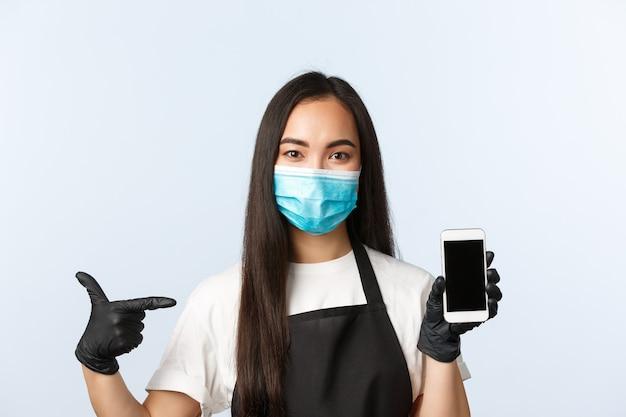 Pandémie de covid-19, café, petite entreprise et concept de prévention des virus. employée asiatique séduisante, employée de café portant un masque médical et des gants pointant sur l'écran du téléphone portable