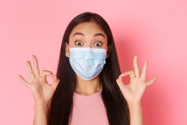 Pandémie covid-19, coronavirus et concept de distanciation sociale. gros plan d'une jolie fille asiatique excitée à la recherche d'un masque médical étonné, montrant un geste correct, recommande le produit ou le lieu parfait.