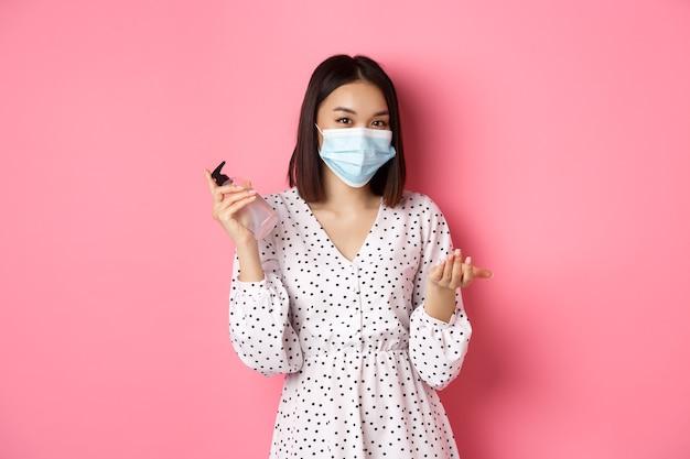 Pandémie de covid et concept de mode de vie jolie femme asiatique se nettoyer les mains avec un désinfectant à l'aide d'un antiseptique et d'un antiseptique.