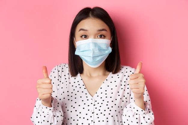 La pandémie de covid et le concept de mode de vie soutenant une femme asiatique en masque facial montrant le pouce levé approuvent un...