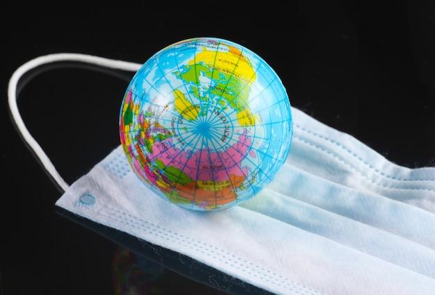 Pandémie mondiale. masque médical avec globe sur fond noir