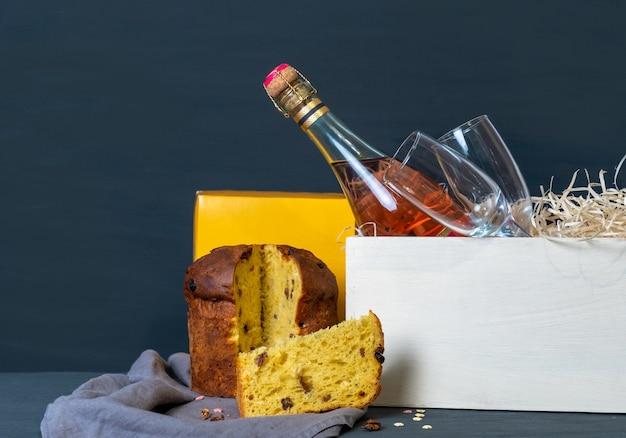 Panetone de pâques italien avec bouteille de champagne et deux verres sur le fond bleu.