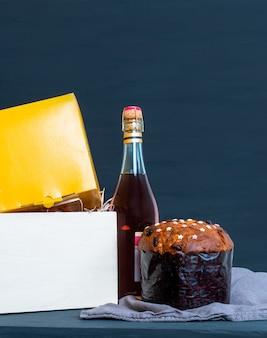Panetone de pâques italien dans un emballage avec une bouteille de champagne sur le fond bleu.