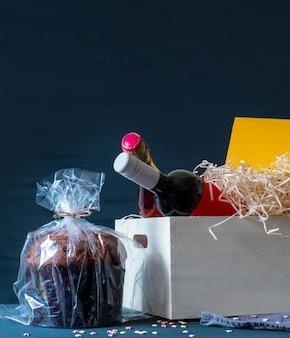 Panetone de pâques italien dans un emballage avec des bouteilles de vin et de champagne sur le fond bleu.