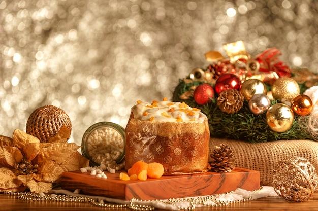Panettone au chocolat blanc avec abricot séché sur table en bois avec des ornements de noël