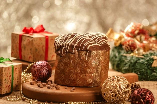 Panettone au chocolat sur table en bois avec des ornements de noël