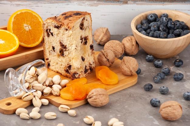 Panettone servi sur une table avec orange, pistache, noix et myrtille