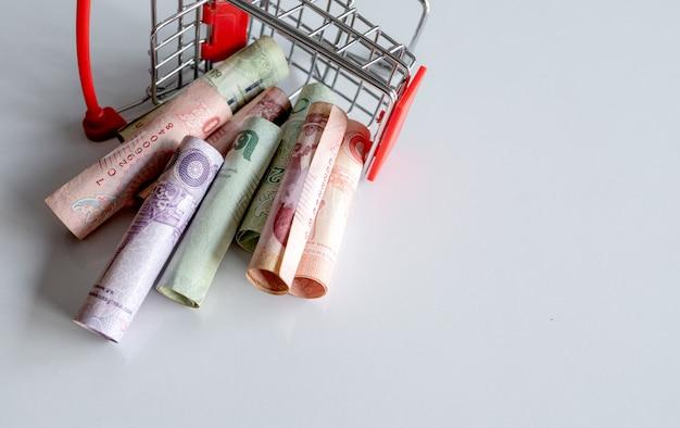 Panier d'achat avec l'argent (argent thaïlandais) à l'intérieur est à l'envers sur blanc. vue de dessus