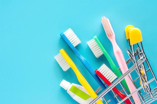Panier d'achat avec brosse à dents et dentifrice sur fond bleu