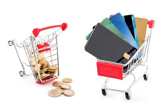 Panier d'achat avec des cartes de crédit et un autre panier plein de pièces en euros qui en tombent sur fond blanc. les cartes de crédit gagnent et l'argent est vaincu. anciens et nouveaux modes de paiement.