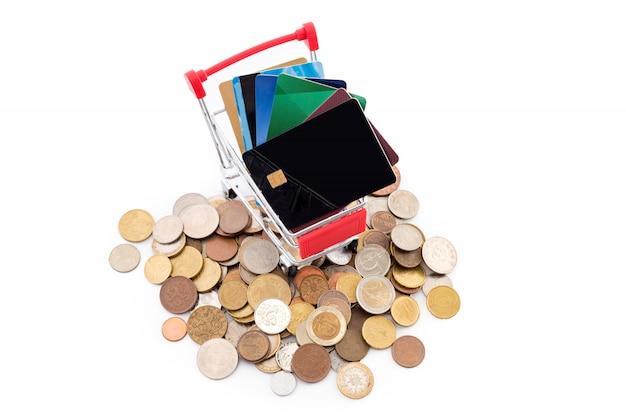 Panier d'achat avec des cartes de crédit monte un tas de pièces sur fond blanc. les cartes de crédit gagnent et l'argent est vaincu. anciens et nouveaux modes de paiement.