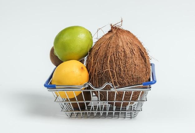 Panier d'achat et fruits tropicaux sur fond blanc. faire du shopping au supermarché. concept de nourriture saine.