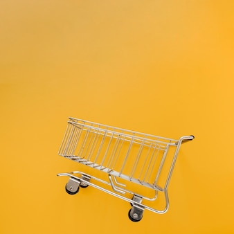 Panier d'achat incliné sur fond jaune