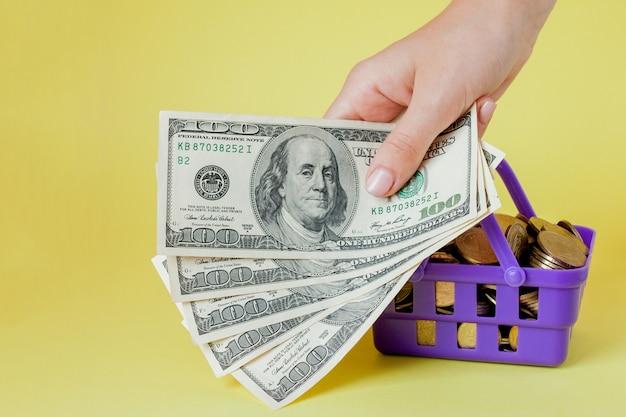 Panier d'achat avec des pièces et des billets d'un dollar dans les mains