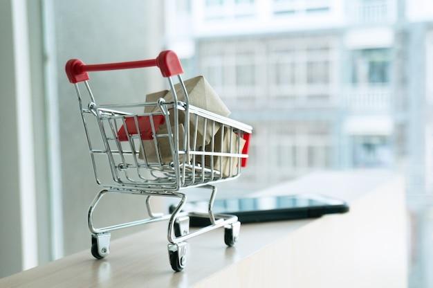 Panier d'achat plein de carton boîtes en papier. chariot à cadeaux la notion de magasinage. focus sélectif