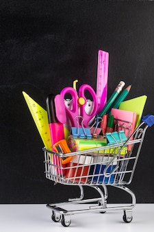 Panier d'achat rempli de fournitures scolaires et d'un tableau