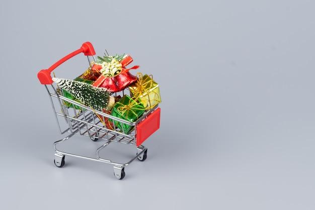 Panier d'achat avec des sapins de noël et des coffrets cadeaux miniatures sur fond gris