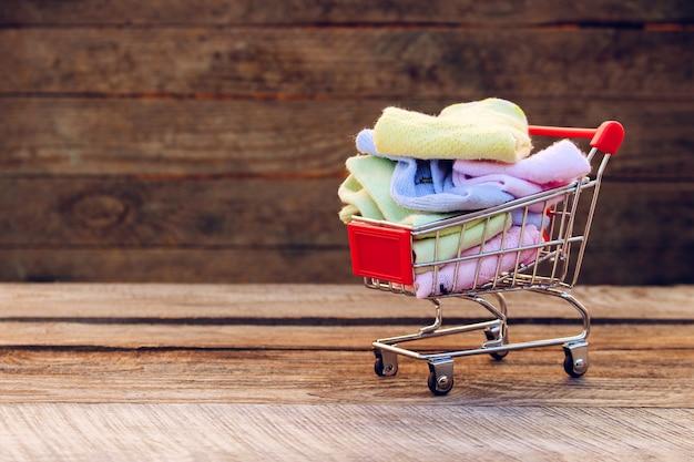 Panier d'achat avec des vêtements sur le vieux fond de bois. image tonique.