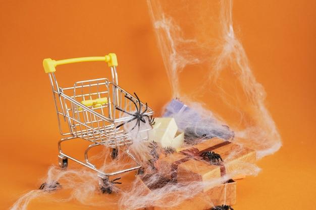 Panier avec araignée et coffrets cadeaux sur fond marron, halloween shopping sur concept, toile d'araignée et araignées sur fond