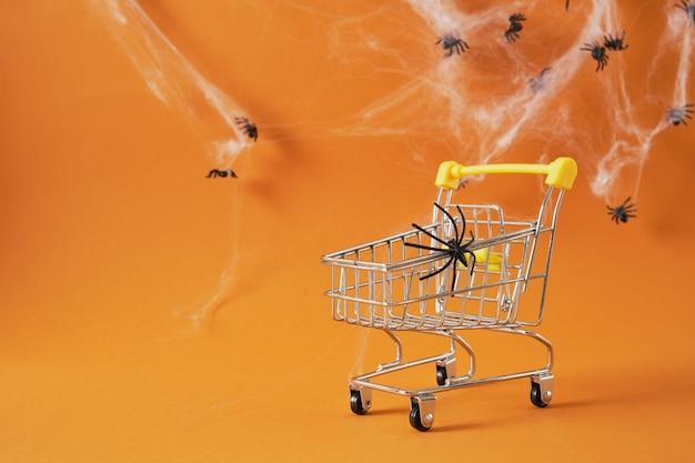 Panier avec araignée sur fond marron, halloween shopping sur concept, toiles d'araignées et araignées sur l'espace de copie d'arrière-plan