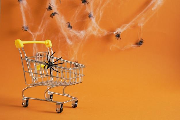 Panier avec araignée sur fond marron, halloween shopping sur concept, toiles d'araignées et araignées sur fond