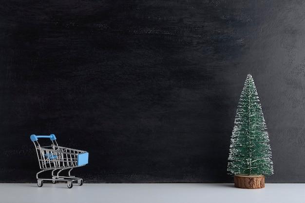 Panier et arbre de noël miniature sur fond noir. achats du nouvel an. espace de copie