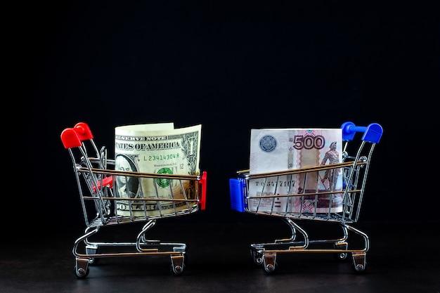 Panier avec de l'argent de différents pays: dollars, roubles sur une surface noire