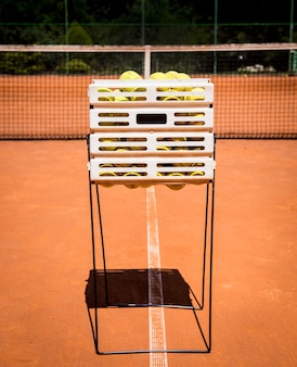 Panier avec des balles de tennis jaunes sur un court de tennis rouge
