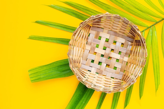 Panier de bambou en bois vide sur des feuilles de palmiers tropicaux sur fond jaune.