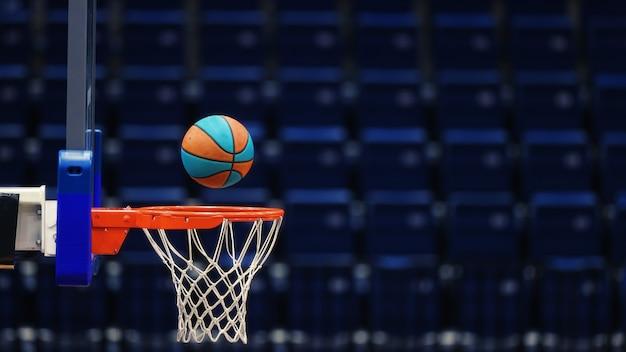 Panier de basket avec un ballon sur les sièges vides de l'arène sportive