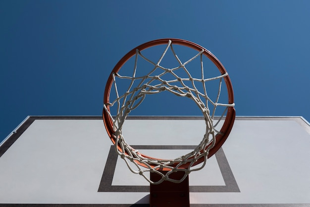 Panier de basket sur un terrain de basket extérieur avec vue en contre-plongée sur fond de ciel bleu