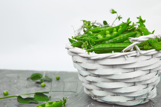 Panier blanc avec pois verts frais sur fond gris.