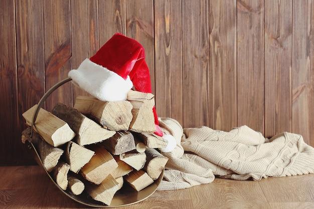 Panier avec bois de chauffage et chapeau de père noël sur fond de bois