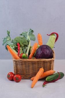 Panier en bois de légumes frais sur une surface blanche.
