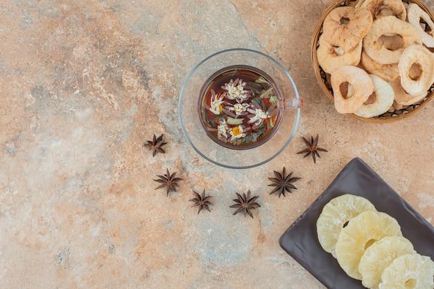 Un panier en bois plein d'ananas séché et une tasse de tisane