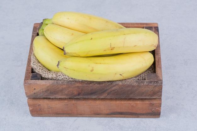 Un panier en bois plein de bananes aux fruits mûrs sur fond blanc. photo de haute qualité