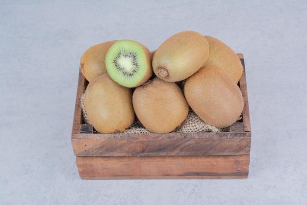 Un panier en bois plein de kiwi frais sur fond blanc. photo de haute qualité
