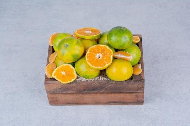 Un panier en bois plein de mandarines tranchées sur fond blanc . photo de haute qualité