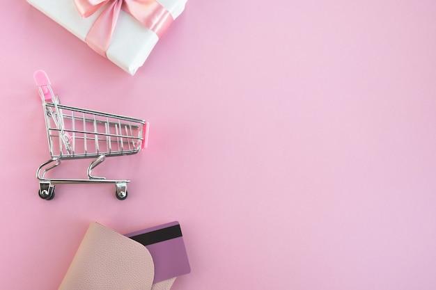 Panier, boîte-cadeau et portefeuille avec carte de crédit sur rose