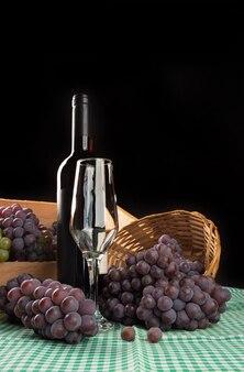 Panier et boîte renversée avec des raisins tombant sur la table avec du vin et un verre sur une nappe à carreaux, surface noire