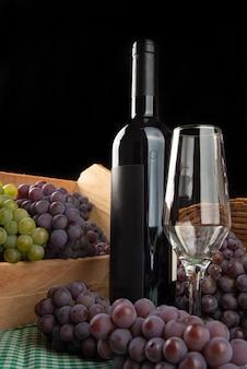 Panier et boîte renversée avec des raisins tombant sur la table avec du vin et un verre sur une nappe à carreaux