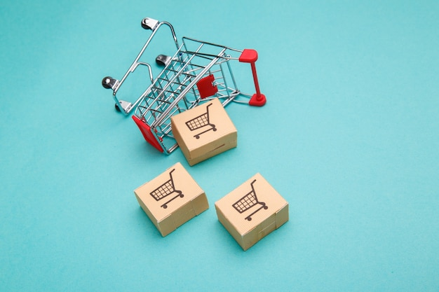 Panier avec des boîtes sur bleu. le concept d'achat et de livraison en ligne.